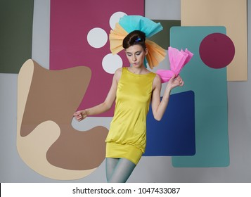 Female model in yellow is actively posing in the studio on an unusual background. Fashion story, Danish - Japanise design. Color composition. Eccentric attire. Short dress, high heels. Blue pantyhose