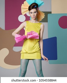 A female model in yellow is actively posing in the studio on an unusual background. Fashion story, Danish design. Color composition. Eccentric attire. Short dress