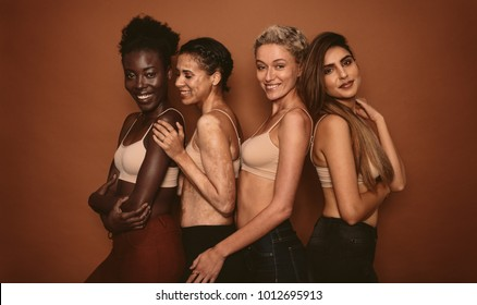 Female models with different skins standing together and smiling. Group of happy young women on brown background.