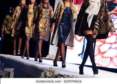 Female models walk the runway in beautiful designer dresses during a Fashion Show. Fashion catwalk event showing new collection of clothes. Unrecognizable people. High heels shoes. Legs only.