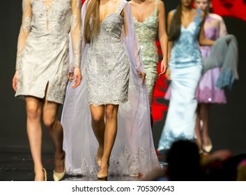 Female models walk the runway in colourful dresses during a Fashion Show. Fashion catwalk event showing new collection of clothes.