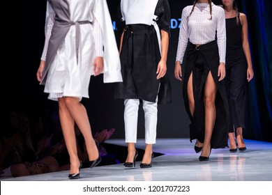 Female models walk the runway in different dresses during a Fashion Show. Fashion catwalk event showing new collection of clothes. Legs and shoes only.