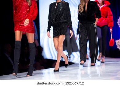 Female models walk the runway in different colorful red dresses during a Fashion Show. Fashion catwalk event showing new collection of clothes.