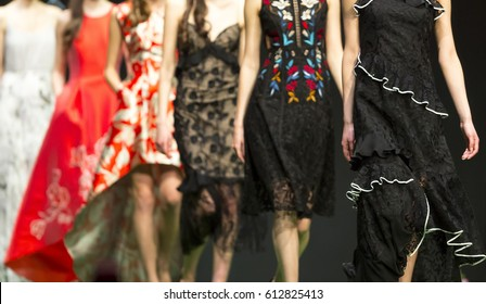 Female models walk the runway in different dresses during a Fashion Show. Fashion catwalk event showing new collection of clothes.