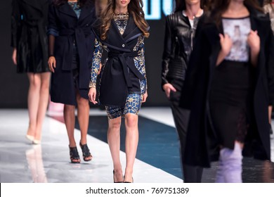 Female models walk the runway in different dresses during a Fashion Show. Fashion catwalk event showing new collection of clothes. In a row.