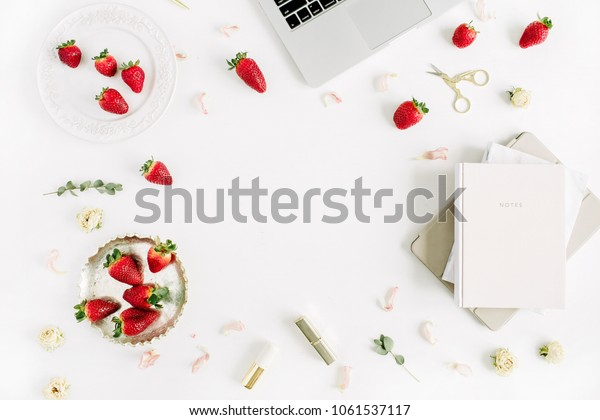 Female modern home office desk with laptop, notebook, lipstick, fresh raw strawberries and rose flower buds on white background. Flat lay, top view. Frame with copy space for text.