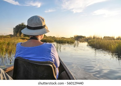 A female in a Mokoro, a wooden boat used in the Okavango Delta in Botswana looking at the river