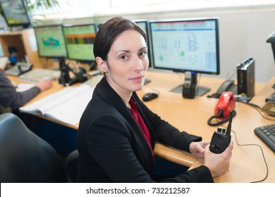 female monitoring guard holding walkie-talkie