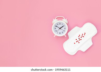 Female monthly pads and white alarm clock on pink background. Concept of women's health and regular menstruation. Copy space