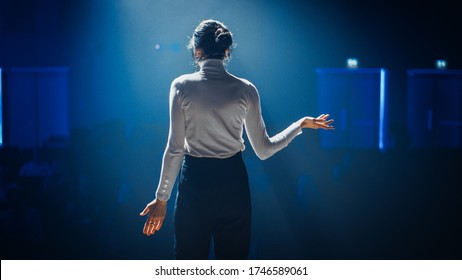 Female Motivational Speaker on Stage, Talking about Happiness, Diversity, Success, Leadership, STEM and How to Be Productive. Woman Presenter Leads Tech Business Conference. Back View Shot