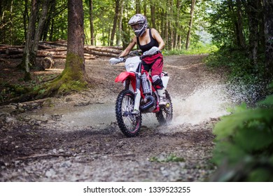 Female motocross rider crossing a forest stream at high speed