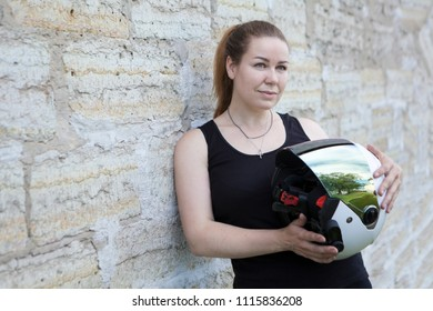 Female motorcyclist posing with white helmet near stone wall, copy space