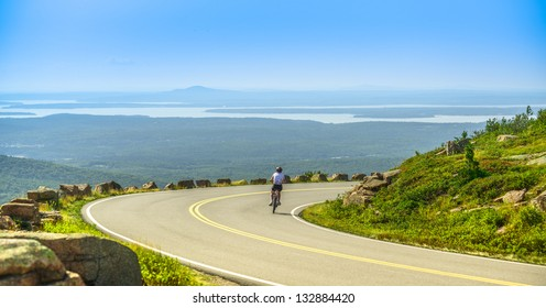 Female mountain bike cyclist riding downhill along Cadillac Mountain road in Acadia National Park, a clear summer day with panoramic view of Acadia National Park (Maine, USA) landscape with lakes.