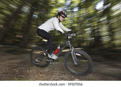 Female mountain biker in a forest with motion blur.