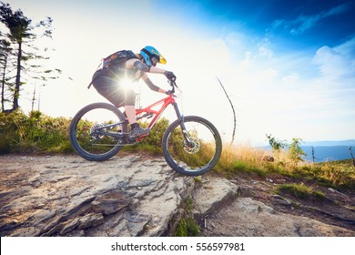 Female mountain biker riding, cycling MTB bike during sunny day in Mountains