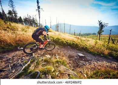 Female mountain biker riding on MTB, fullsuspension bike on single track in mountains