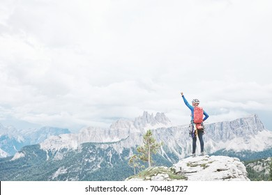 Female mountaineer with backpack, helmet and harness with climbing gear raising her hand celebrating successful climb during summer day in Dolomite Alps - mountaineering or sport climbing concept