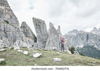 Female mountaineer with backpack, helmet and harness with climbing gear preparing for ascent during summer day in Cinque Torri, Dolomite Alps, Italy - mountaineering or sport climbing concept