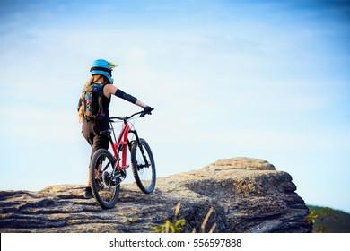 Female MTB mountain biker enjoys the view during cycling trip