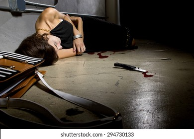 female murder victim laying on a dark alley with a bloody knife.  the crime scene is a dark street alley.
