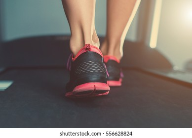 Female muscular feet in sneakers running on the treadmill at the gym.