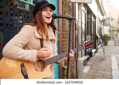 Female Musician Busking Playing Acoustic Guitar And Singing Outdoors In Street