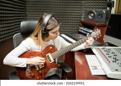 Female musician playing guitar in recording studio room  composing music