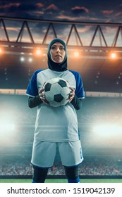 Female muslim soccer player in hijab standing with a ball on a professional stadium