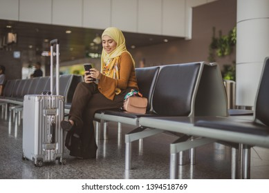 Female Muslim Traveler looking at her phone at the departure hall.