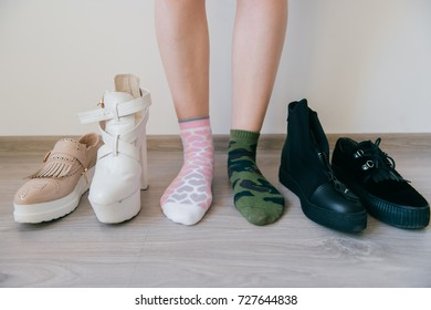 Female naked legs standing on floor. Women`s feet in mismatched cotton socks. Odd unusual weird unrecognizable bizarre kinky girl. Brutal and tenderness concept. Different big choice of footwear