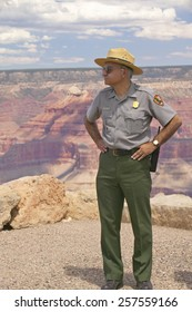 Female National Park ranger looking at South Rim of Grand Canyon National Park in mid-summer in Arizona