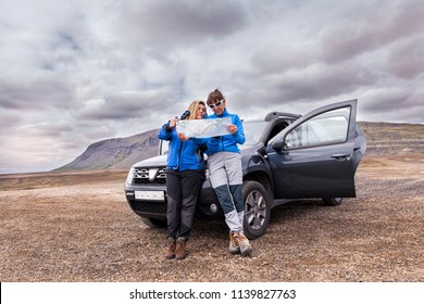 female naturalist photographers searching for the right road on the map in a wild area of Iceland