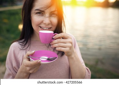 female near lake or river and keeps cup of coffee; woman drinks hot tea on the beach near water in rays of sunset;