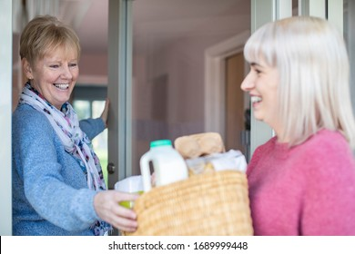 Female Neighbor Helping Senior Woman With Shopping Whilst Self Isolating During Coronavirus