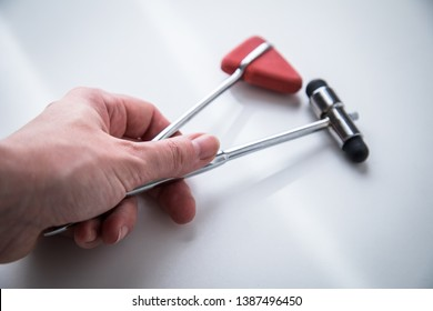 Female Neurologist working with Buck and Tylor reflex hammer for examination