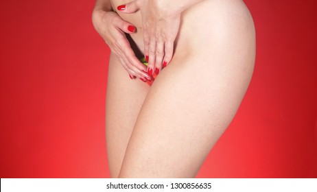 female nude hips on a red background with a slice of watermelon in the perineum.