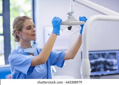 Female nurse adjusting dental light in clinic