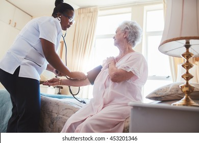 Female nurse checking blood pressure of a senior woman sitting on bed at home. Home carer checking patients blood pressure at home.
