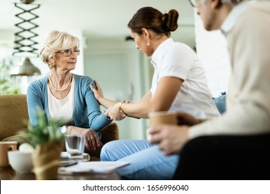 Female nurse communicating with senior woman while being in home visit. Focus is on senior woman.