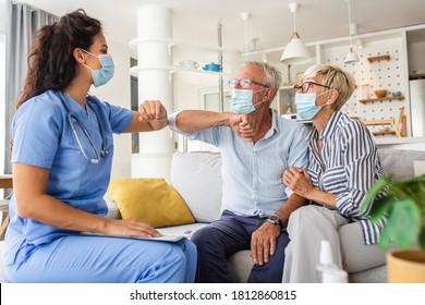 Die weibliche Krankenschwester grüßt mit Senioren Patienten mit Maske während eines Hausbesuchs.