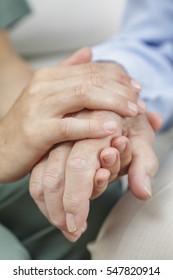 Female nurse holding the hand of a senior man