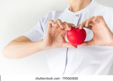 Female nurse is holding a red heart shape. Health, Insurance and love concept