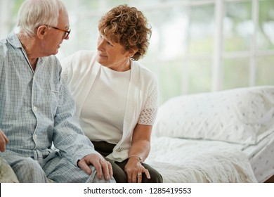Female nurse listening to a senior patient while sitting next to him on the edge of a bed.