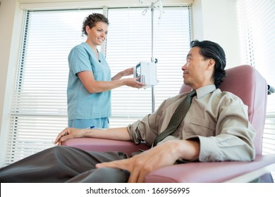 Female nurse looking at patient while adjusting IV machine for chemotherapy in hospital room
