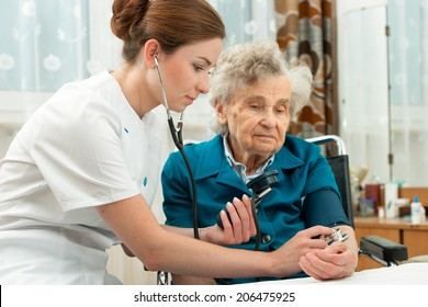Female nurse measuring blood pressure of senior woman