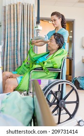 Female nurse removing straps from hydraulic lift with patient on wheelchair in hospital