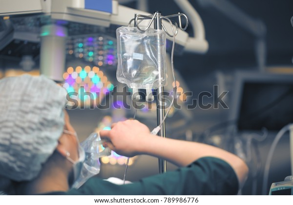 Female nurse replacing solution bags in the drip system in the operating room.