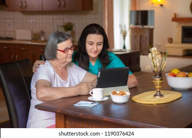 Female nurse and senior woman using tablet PC in kitchen at nursing home.