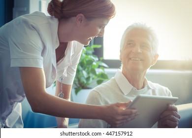 Female nurse showing medical report to senior man on digital tablet at home