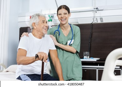 Female Nurse Standing By Senior Patient In Rehab Center